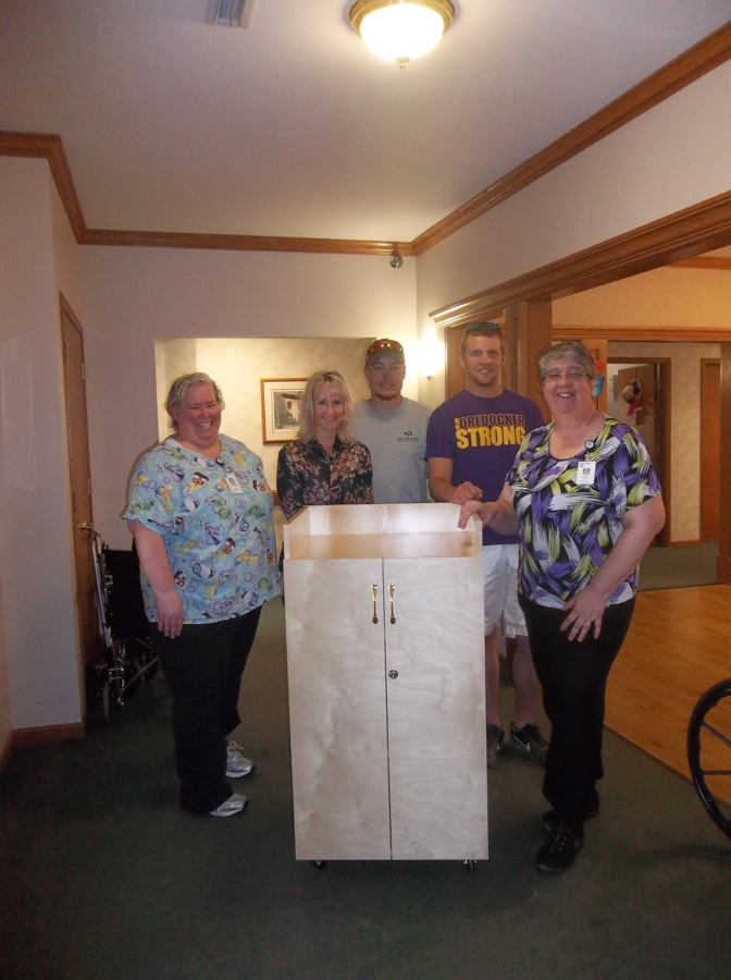 Beaver Dam students and staff stand with donated storage cabinet