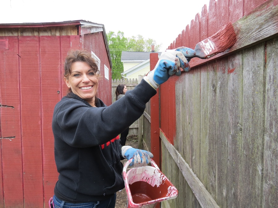Female student paints fence with red paint