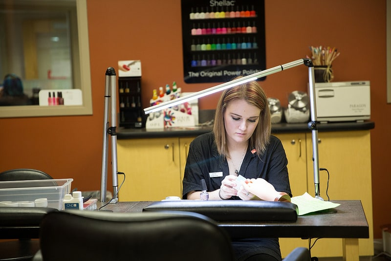 Katie Klettke works at manicure station