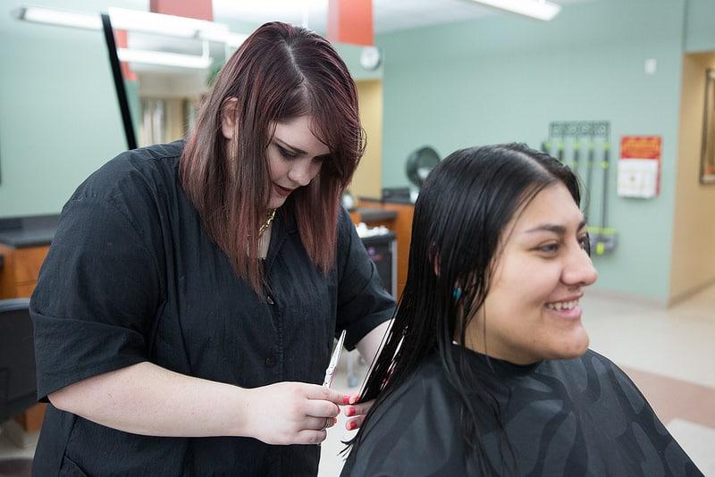 Student styles hair in Moraine Park salon