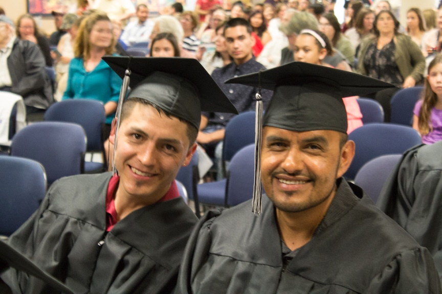 Two male students smile at GED-HSED graduation ceremony