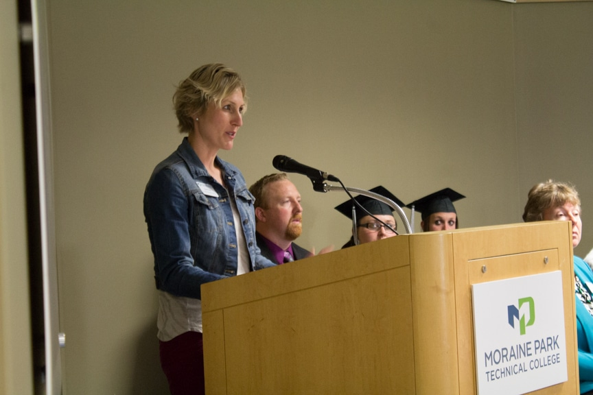 Female staff member speaks at podium at GED-HSED Gradudation Ceremony