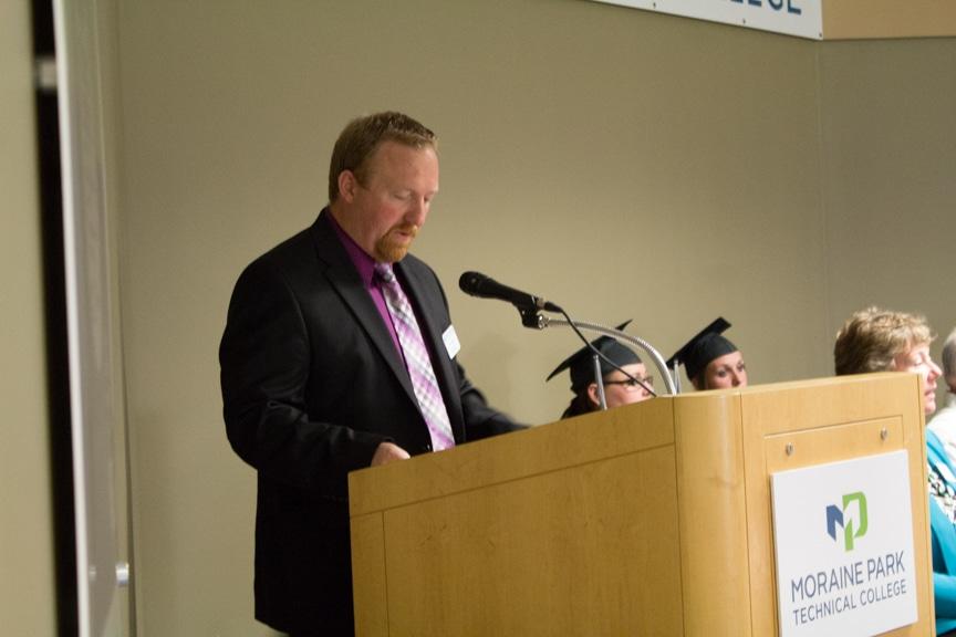 Male staff member speaks at podium at GED-HSED Gradudation Ceremony