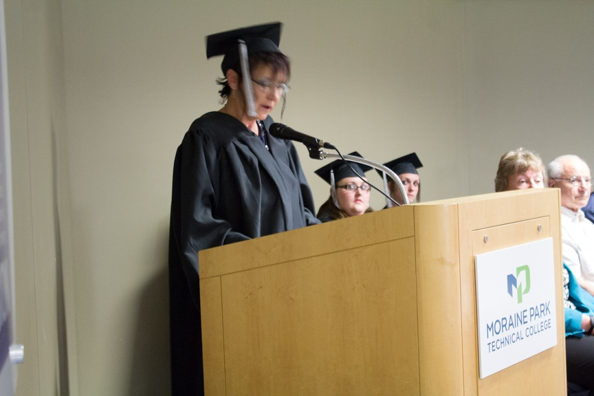 Female graduate talks at podium at GED-HSED Gradudation Ceremony