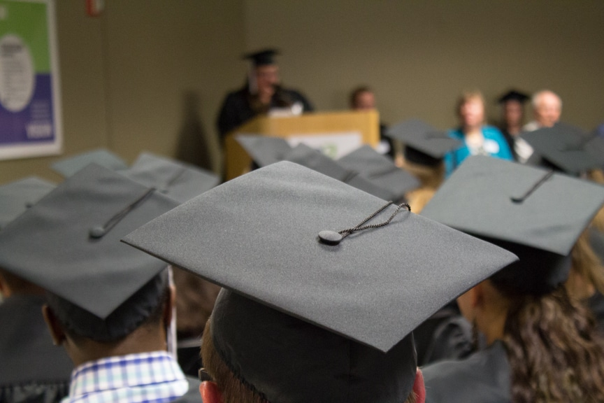 A graduate cap in focus while student speaker talks in background at GED-HSED Gradudation Ceremony