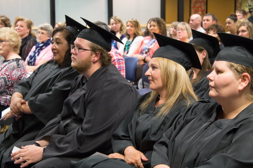 Graduates sit together and listen to speeches