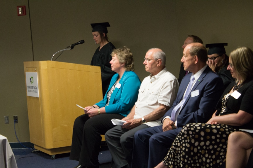 Student speaks from podium at GED-HSED Gradudation Ceremony while college officials listen nearby