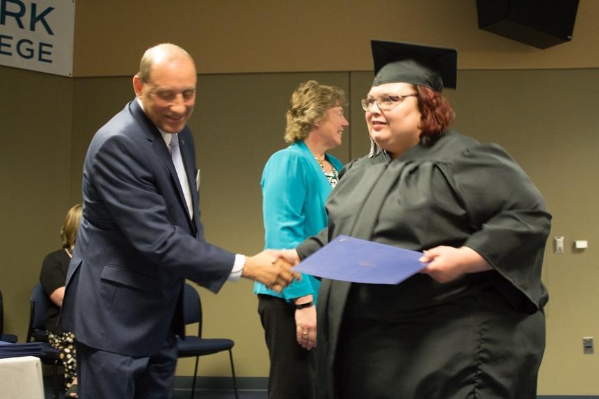 Female graduate recieves diploma at GED-HSED Gradudation Ceremony