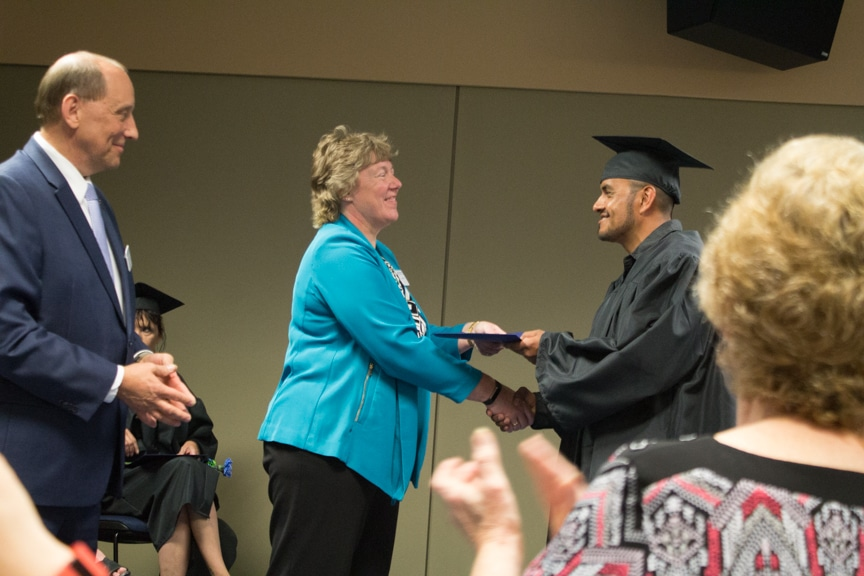 Male graduate shakes president Bonnie Baerwald hand at GED-HSED Gradudation Ceremony