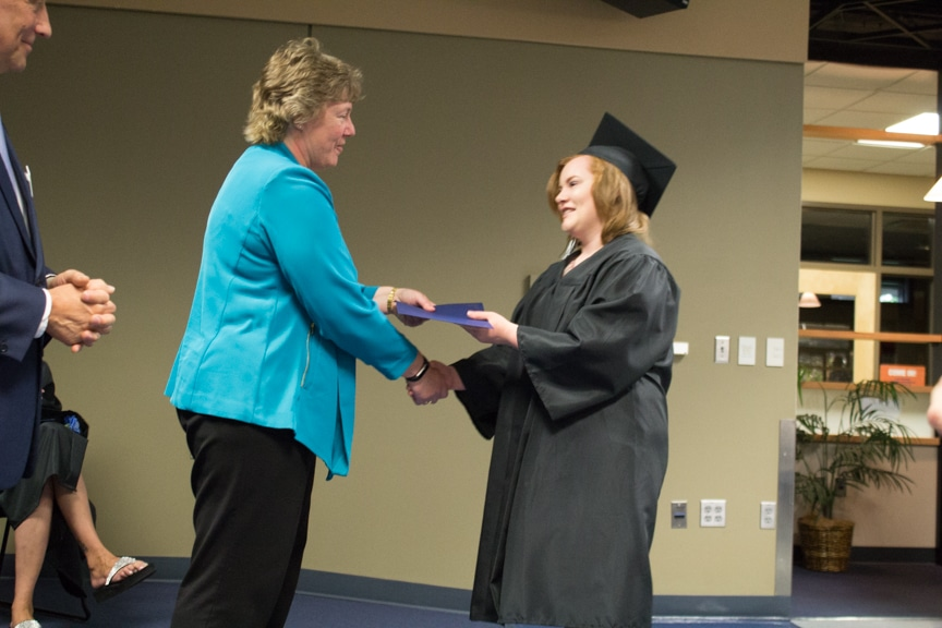 Female graduate shakes president Bonnie Baerwald hand at GED-HSED Gradudation Ceremony