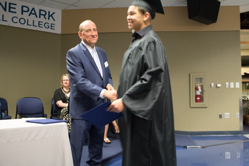 Graduate shakes Jim Eden hand while recieving diploma at GED-HSED Gradudation Ceremony