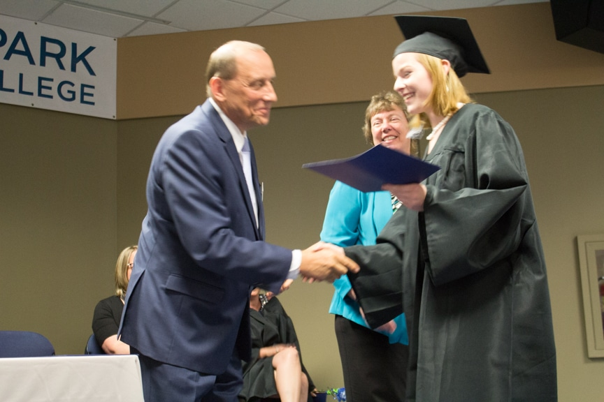Female graduate smiles while recieving diploma at GED-HSED Gradudation Ceremony