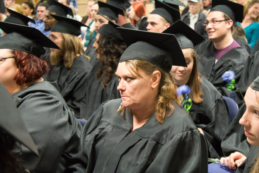 Female graduate sits and listens to speeches at GED-HSED Gradudation Ceremony