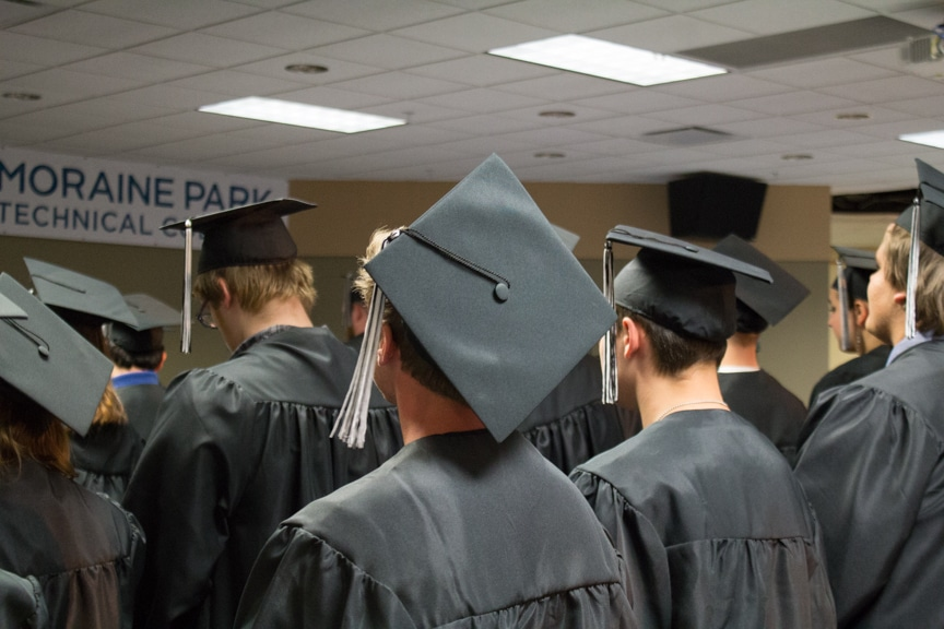 Graduates stand in cap and gowns at GED-HSED Gradudation Ceremony