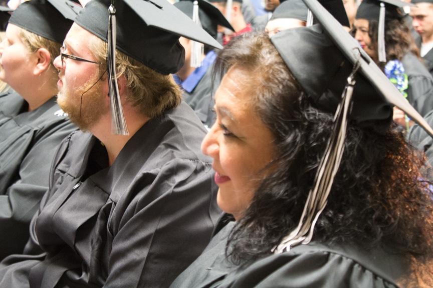 Graduate smiles in crowd at GED-HSED Gradudation Ceremony