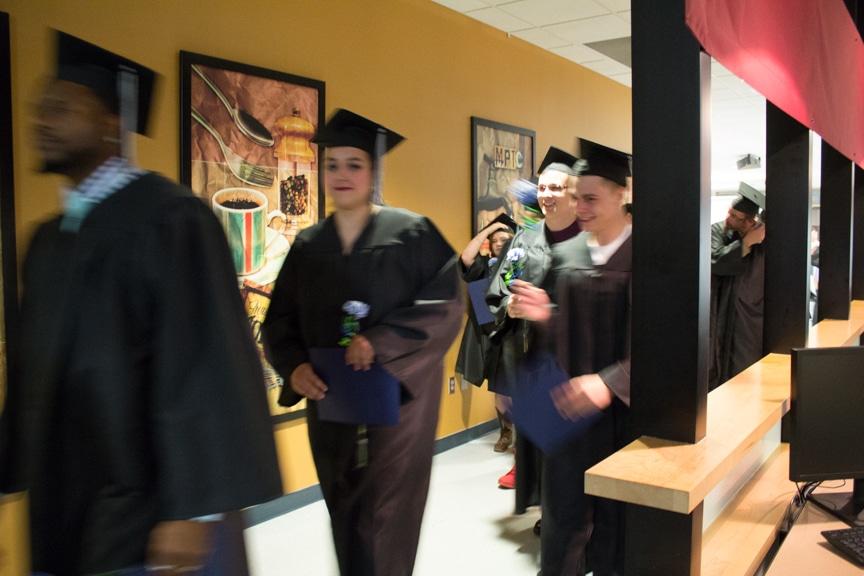 Graduates walk down halway holding diplomas after GED-HSED Gradudation Ceremony