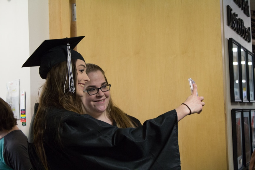 Two graduates take selfie picture together at Moraine Park GED-HSED graduation ceremony