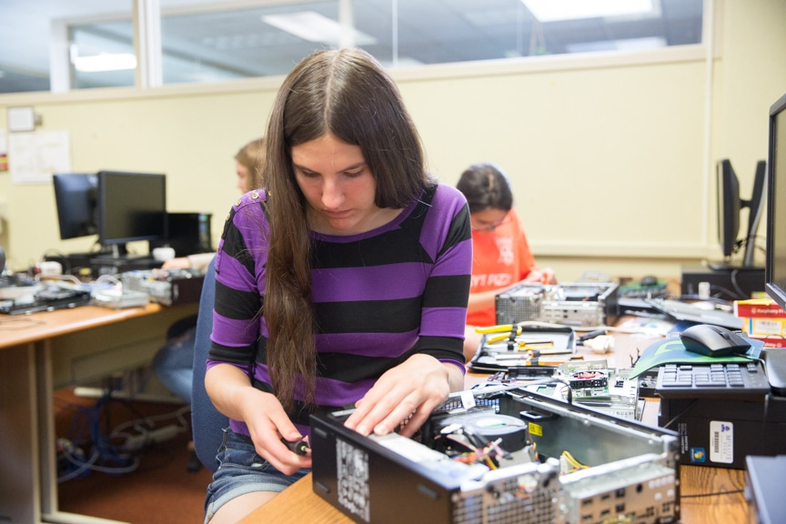 Girl assembles computer towers at Moraine Park Girls Make IT Happen summer camp