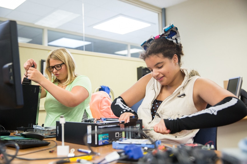 Two girls try to assemble computer tower at Moraine Park summer camp