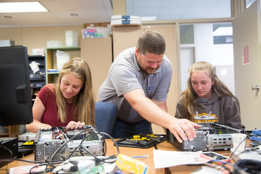 Instructor helps girls put together computer tower parts at Moraine Park summer camp