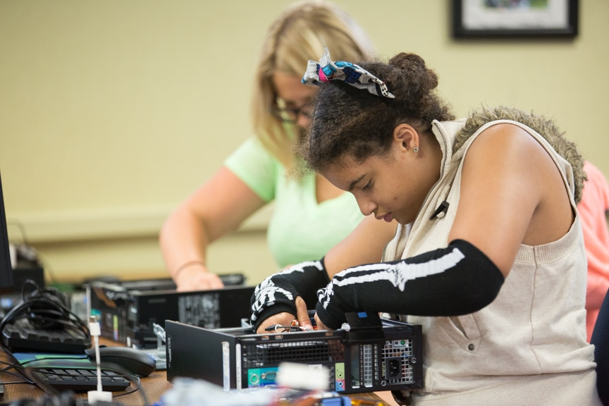 Girl works on assembling computer at Moraine Park summer camp