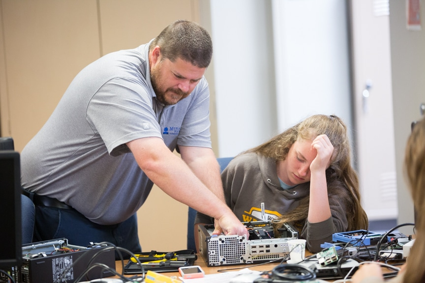 Instructor helps girl trying to assemble PC computer tower at Moraine park summer camp