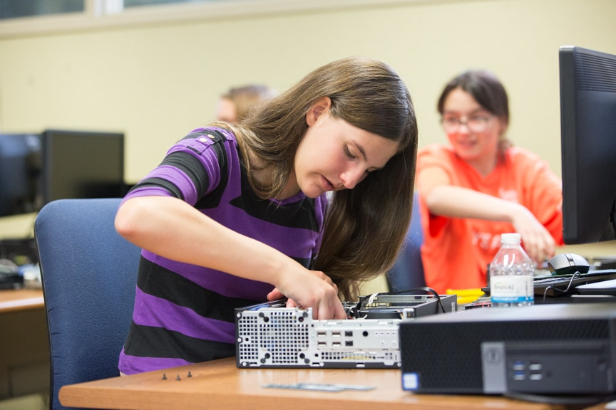 Girl tries to assemble computer tower parts at Moraine Park summer camp