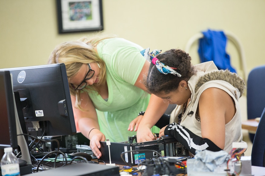 Two girls work on assembling computer tower at Moraine Park summer camp