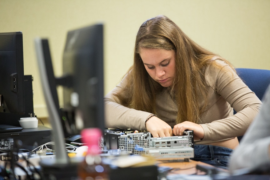 Girl works on computer tower assembly at Moraine Park summer camp