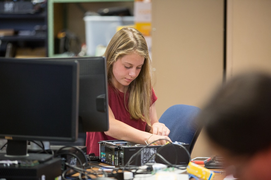 Girl works on assembling PC computer tower
