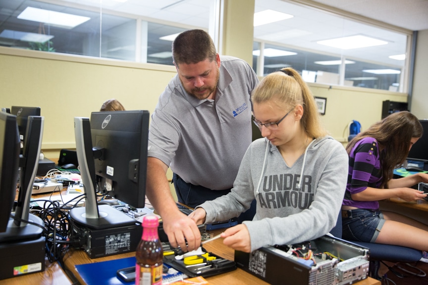 Instructor helps girl put together computer tower parts at Moraine Park summer camp