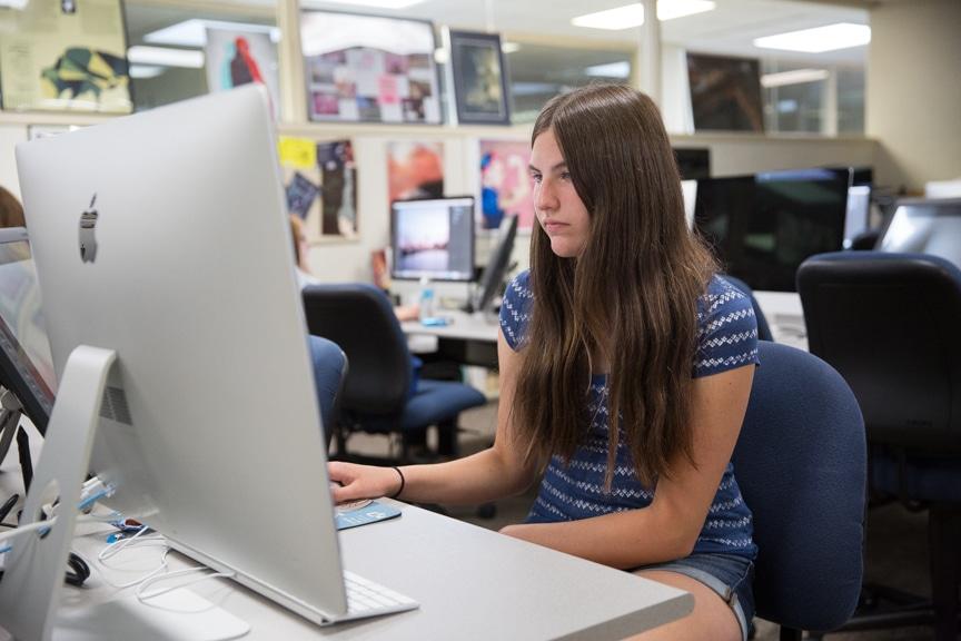 Girl works on iMac computer at Moraine Park Girls Make IT Happen camp