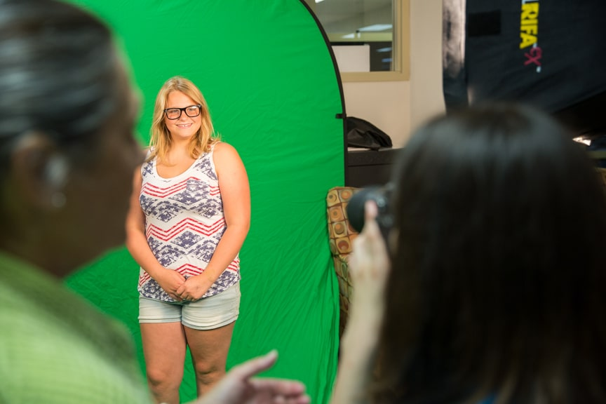 Girl takes photo of another student in front of green screen during Moraine Park summer camp
