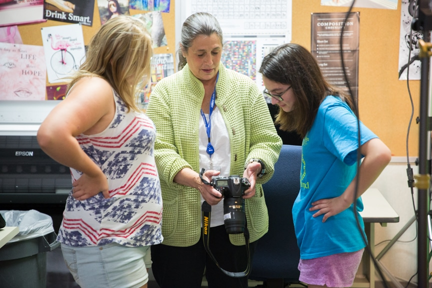 Girls review photos on camera during photography activity at Moraine Park summer camp