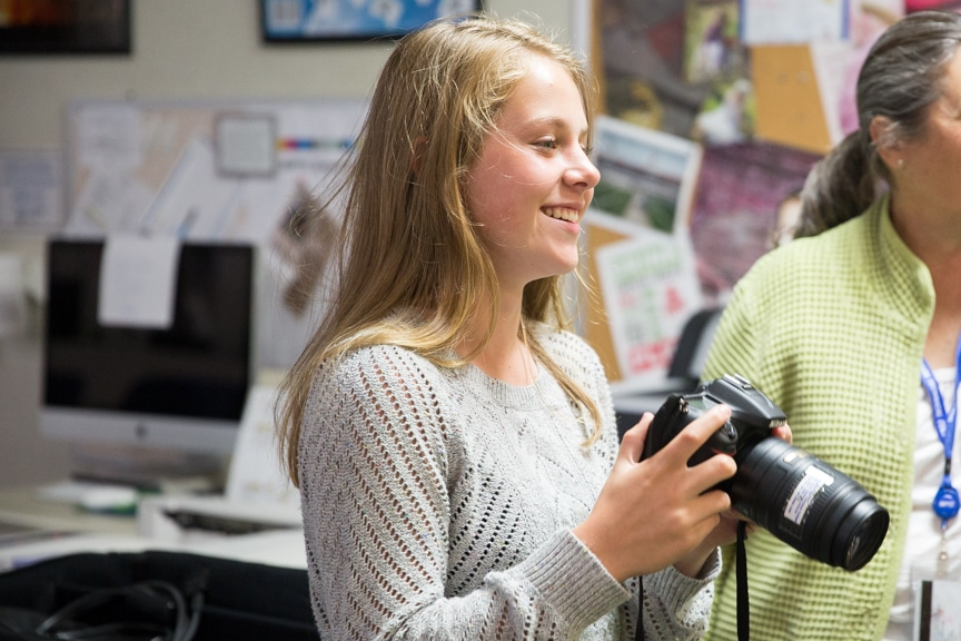 Girl smiles while holding camera during Moraine Park summer camp activity