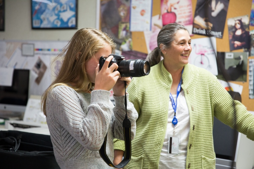 Girl take pictures with camera during Moraine Park summer camp activity