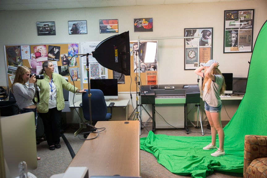 Girl photographs fellow student in front of green screen during Moraine Park summer camp activity