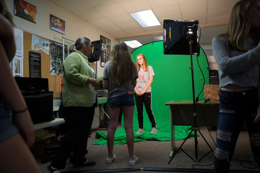 Group of students watch on as girl poses in front of green screen during photography activity at Moraine Park summer camp