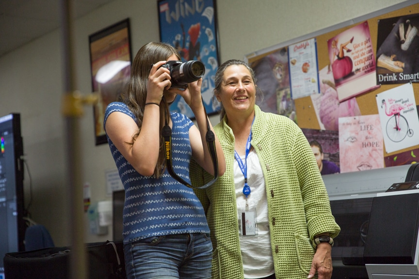 Instructor helps girl with photography project at Moraine Park summer camp