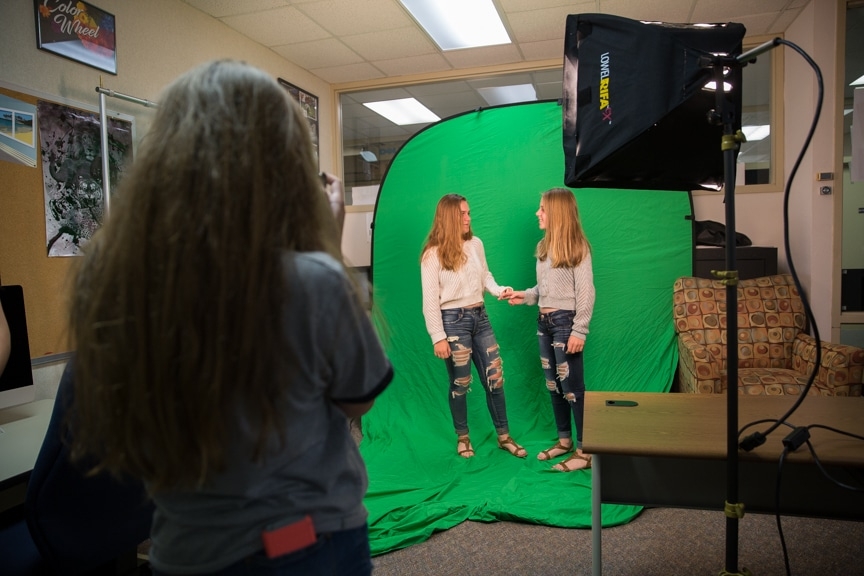 Two girls pose in front of green screen during photography activity at Moraine Park summer camp