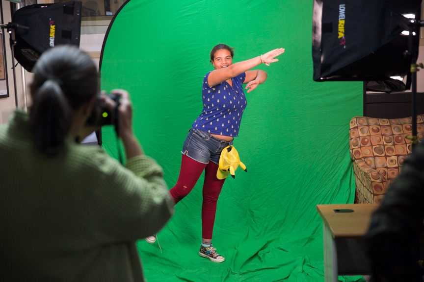 Girl poses in front of green screen during photography activity at Moraine Park summer camp