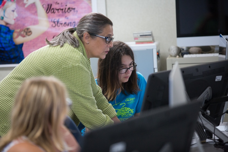 Instructor helps girl with graphic design project on iMac computer at Moraine Park summer camp