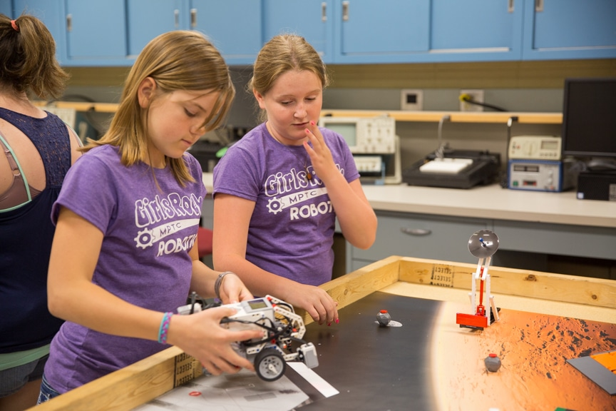 Two girls ready lego robot for demonstration at Moraine Park summer camp