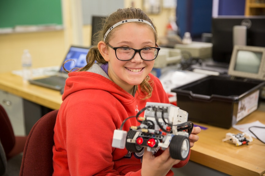 Girl smiles and holds up robotics project at Moraine Park summer camp