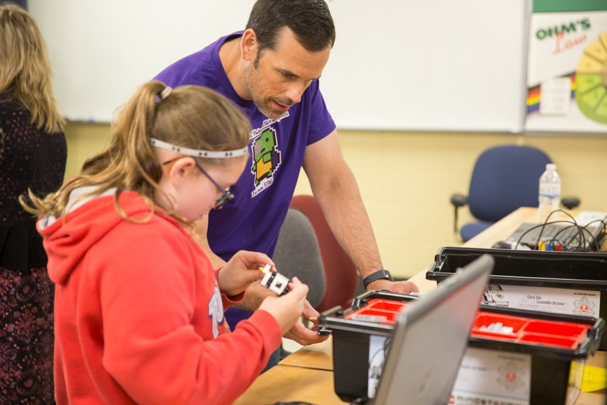 Instructor help girl with robotics project