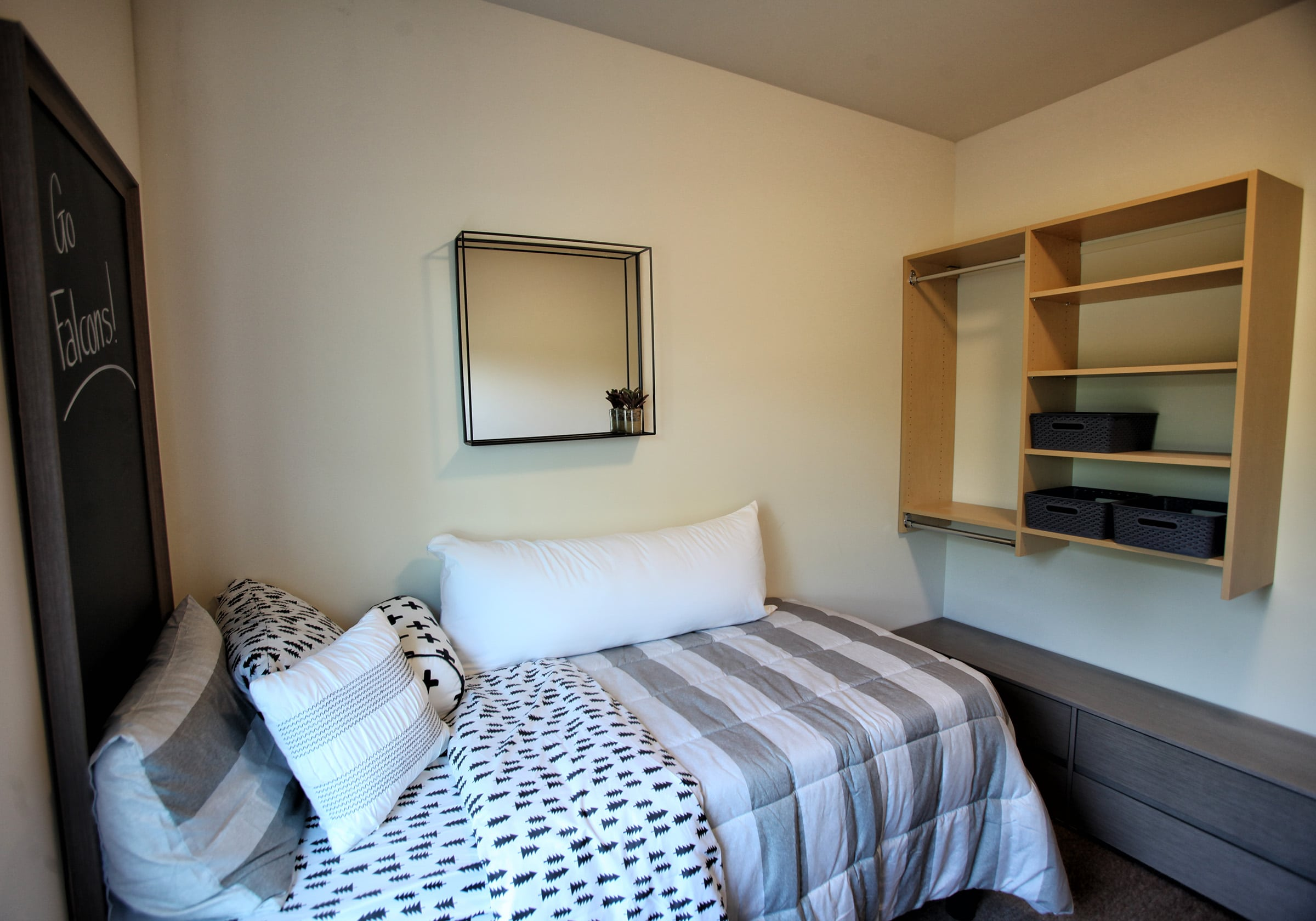 Vue bedroom with shelf on wall and bed