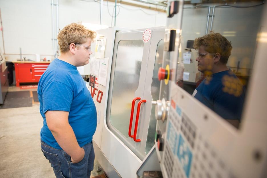 Boy stares into CNC machine at Moraine Park West Bend campus