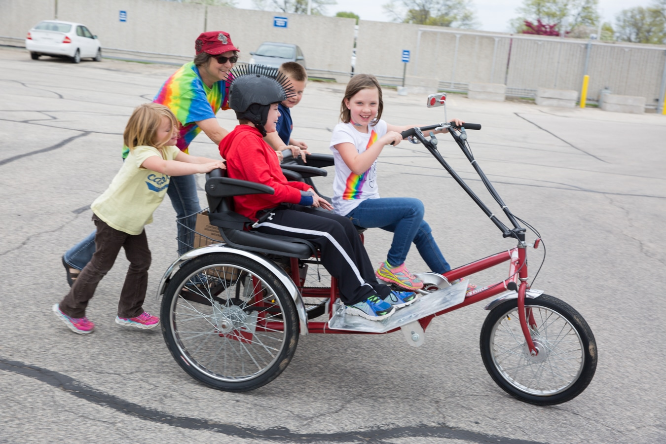 Mason and a girl on trike with mother and two children behind