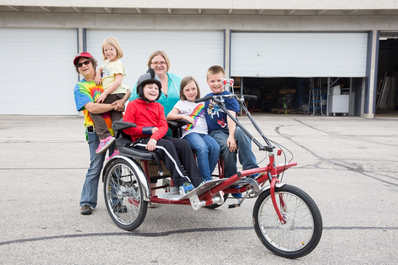 Mason and two other children on trike with two mothers behind