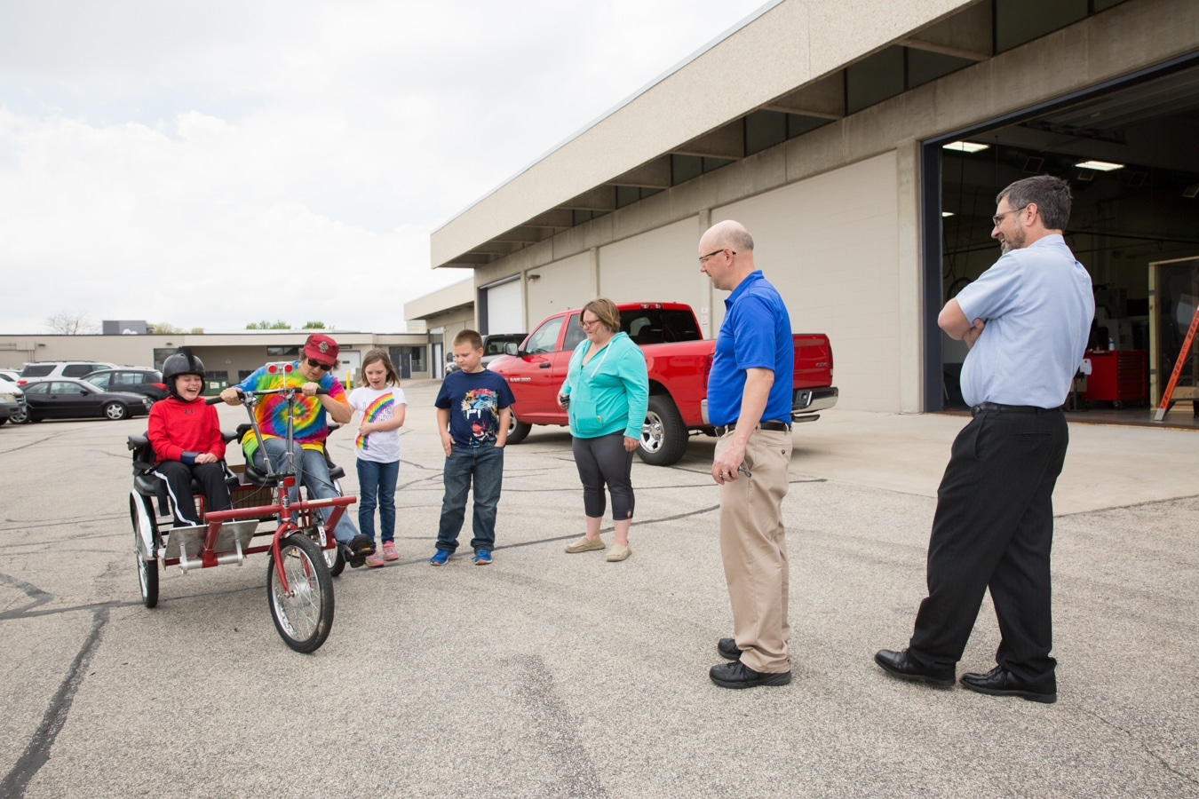 Mason on trike with instructor and other children onlooking